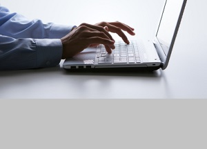 Silhouette of male hands typing on a laptop